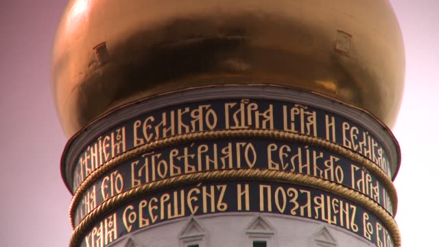 gold lettering encircles the base of a gold onion dome atop the cathedral of the assumption in moscow. available in hd. - onion dome stock videos and b-roll footage