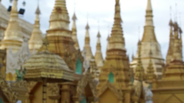 gold pagodas in a monestary in yangonm, myanmar - dissolvenza in chiusura video stock e b–roll