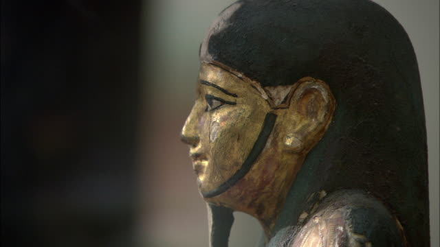 gold paint covers the carved face of an ancient egyptian sarcophagus. - 古代の遺物点の映像素材/bロール