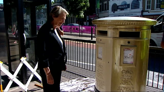 Gold postbox in Stratford ENGLAND London Stratford EXT Postbox being painted gold by workman / Closeup shot of 'ER Royal Mail' in gold paint / PULL...
