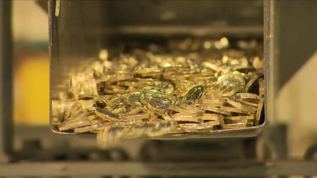 gold pound coins falling from a conveyer belt - royal mint stock videos & royalty-free footage