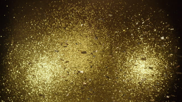 SLO MO Gold sequins blown in front of gold sequin background