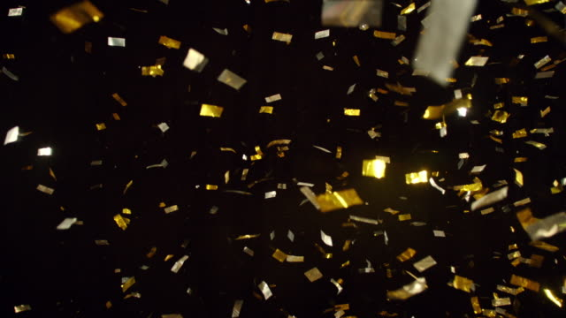 slo mo gold sequins falling and sparkling - scintillante video stock e b–roll