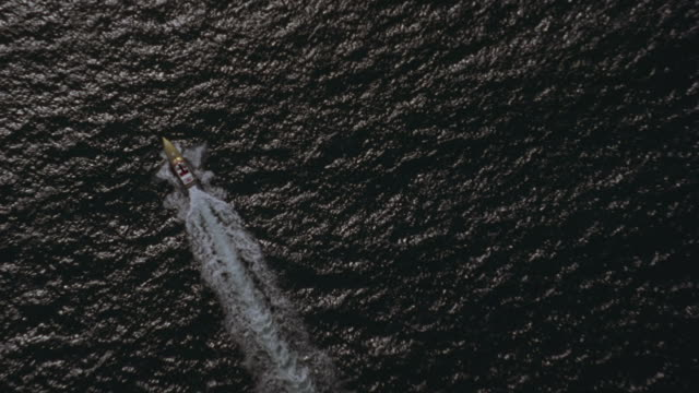 A gold speed boat races across the ocean.