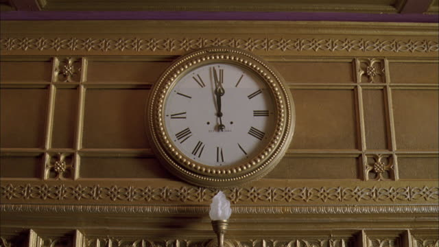 ms gold wall clock showing twelve o'clock - römische zahl stock-videos und b-roll-filmmaterial