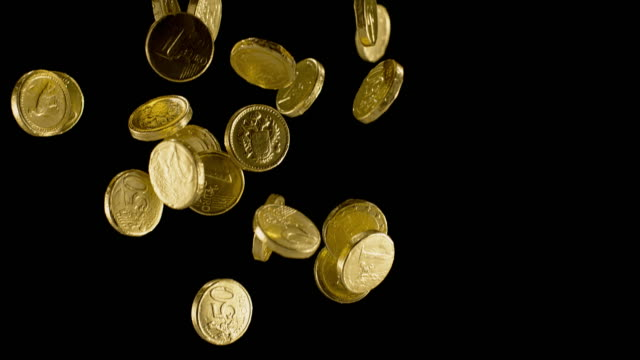 slo mo ld gold wrapped chocolate coin falling on black background - coin stock videos & royalty-free footage