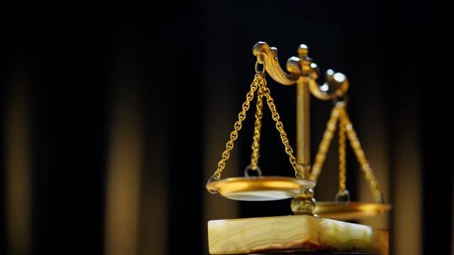 黒の背景に黄金の真鍮のバランス。重量バランス, 法の正義の象徴, 天秤座, 決定 - 正義の天秤点の映像素材/bロール