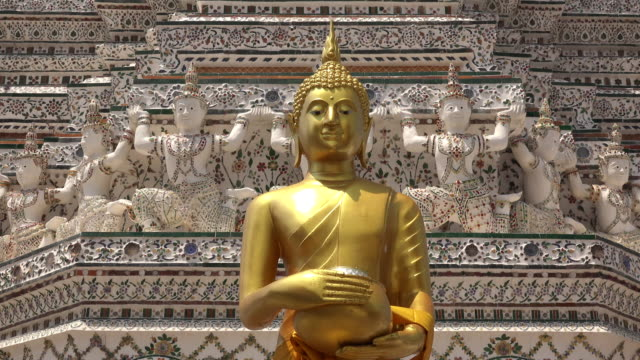 Golden buddha statue in front of temple at Wat Arun in Bangkok, Thailand