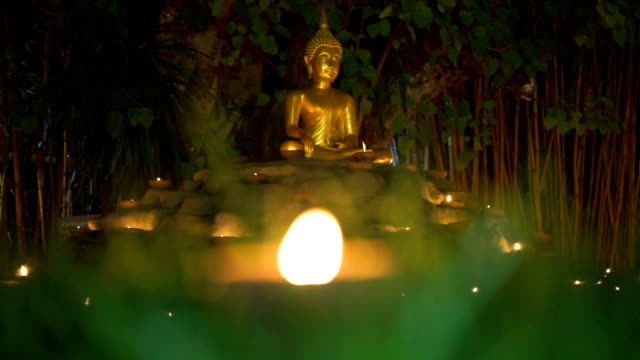 golden buddha statue in meditation sitting pose with grass and candle - mack2happy stock videos and b-roll footage