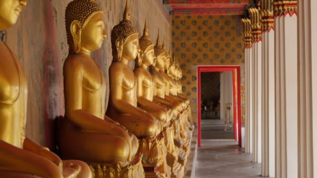 golden buddhas at riverside temple of wat arun (temple of dawn), bangkok, thailand, southeast asia, asia - buddha stock videos & royalty-free footage