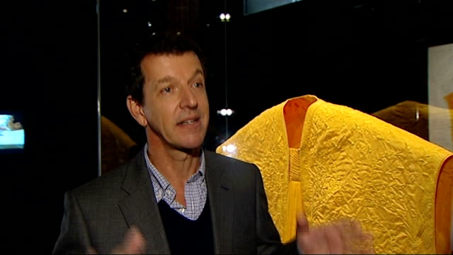 Golden cape made from spider silk on display at VA ENGLAND London Victoria and Albert Museum INT Simon Peers and Nicholas Godley chatting Close shot...
