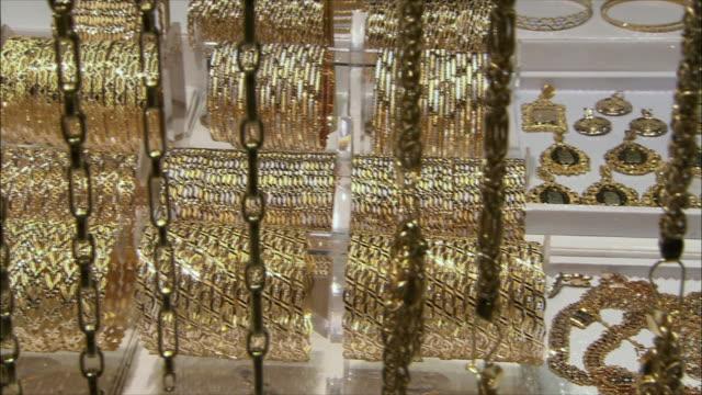 vídeos de stock, filmes e b-roll de cu pan golden chains and bracelets at jewelry store display in grand bazaar, isfahan, iran - vitrine de varejo