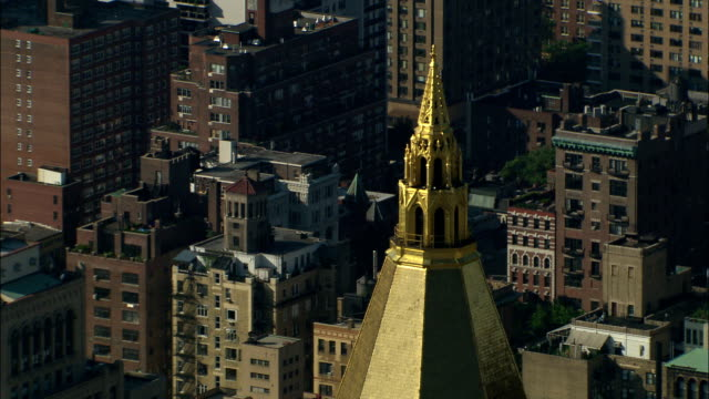 a golden church steeple gleams in the sun amid tall buildings in new york city. - steeple stock videos & royalty-free footage