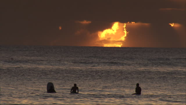 golden clouds glow above waikiki beach where vacationers swim and surf. - powerful stock videos and b-roll footage