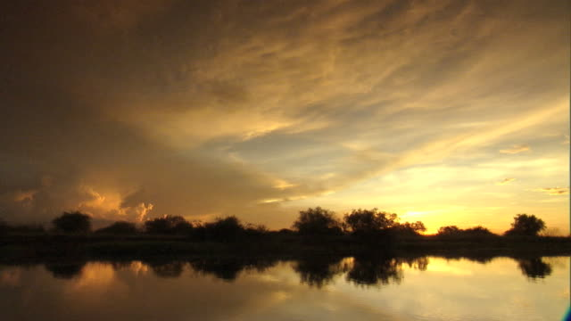 Golden clouds spread across the sky above the Zambezi River in Zambia, South Africa.