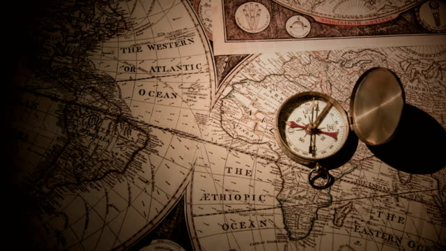 golden compass on antique map - esplorazione video stock e b–roll