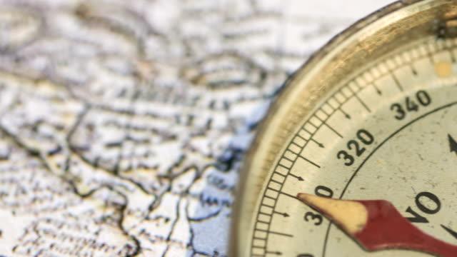 vídeos de stock, filmes e b-roll de bússola de ouro no mapa antigo - compasso
