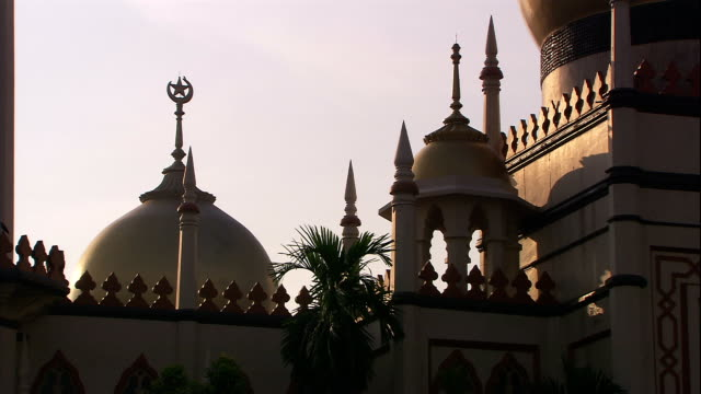 a golden dome and the islamic star and crescent top the sultan mosque in singapore. - sultan mosque singapore stock videos and b-roll footage