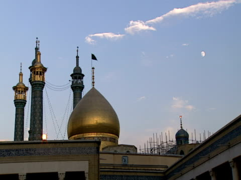 la golden dome and towering minarets of mosque against blue evening sky / qom, iran - shi'ite islam stock videos & royalty-free footage