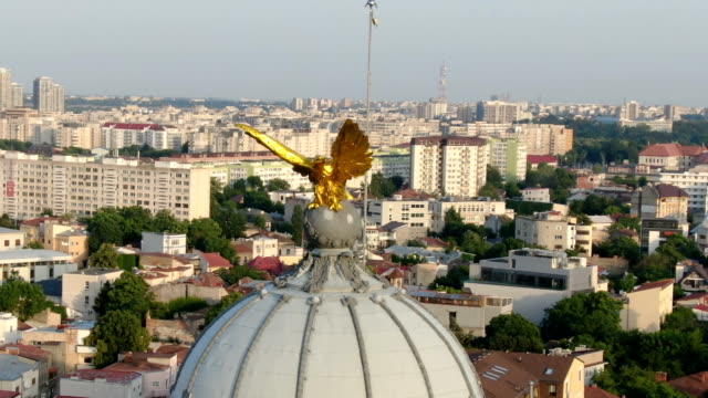 golden eagle statue on top of church with bucharest city in back/ aerial drone view - golden eagle stock videos & royalty-free footage