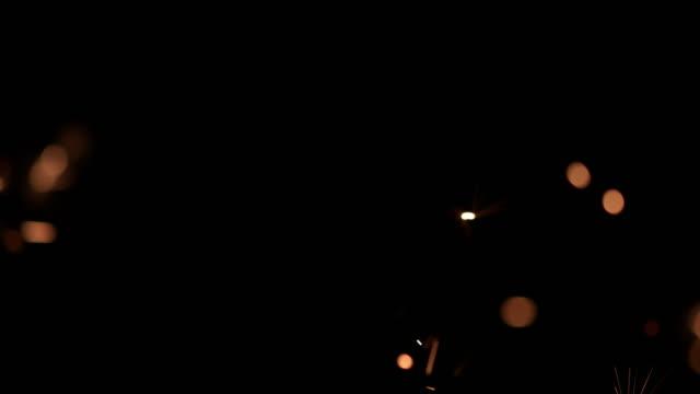 vidéos et rushes de ms super slow motion étincelles de feu d'or contre le ciel noir - black background