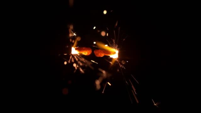 vidéos et rushes de ms super slow motion feux d'artifice d'or étincelles contre le noir - cierge magique
