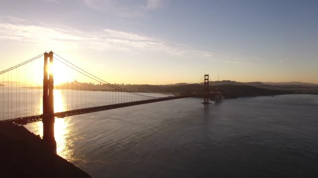 golden gate bridge sunrise pull away reveal aerial, 4k, 1/30s, 11of10, stock video sale - drone - san francisco california stock videos & royalty-free footage
