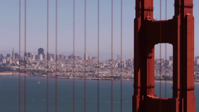 golden gate bridge suspension wires and pillars with sf downtown in background - spoonfilm stock-videos und b-roll-filmmaterial