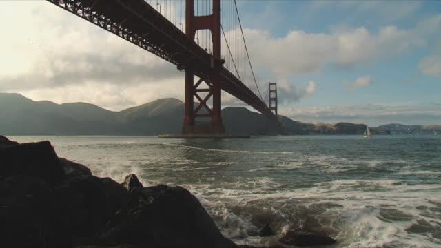 vidéos et rushes de ws golden gate bridge, waves crashing against rock in foreground / san francisco, california, usa - baie de san francisco