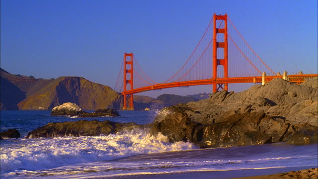 FAST MOTION, WS, Golden Gate Bridge, waves crushing against rocks on Baker Beach in foreground, San Francisco, California, USA
