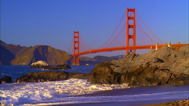 WS, Golden Gate Bridge, waves crushing against rocks on Baker Beach in foreground, San Francisco, California, USA