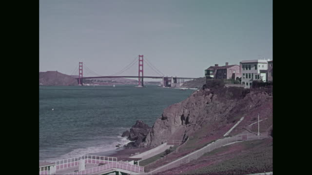 ws pan golden gate bridge with seashore and buildings / san francisco, california, united states - 1960 stock videos & royalty-free footage