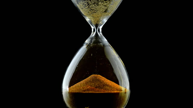 slo mo ld golden grains of sand falling through an hourglass - glass material stock videos & royalty-free footage