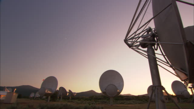 A golden haze outlines satellite dishes near California mountains at sunset.