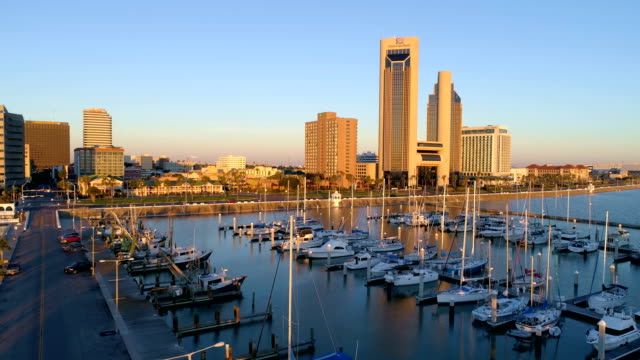 golden hour glow off towers and downtown skyscrapers of corpus christi , texas , usa aerial drone view - corpus christi texas stock videos & royalty-free footage