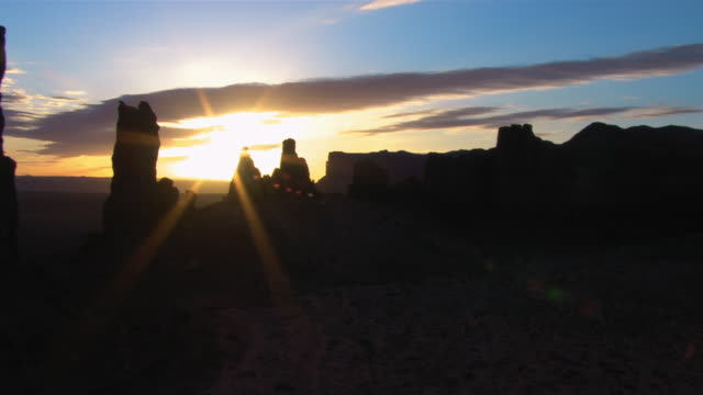 A golden hour sun glows behind the Totem Pole rock formations in Monument Valley, Arizona.