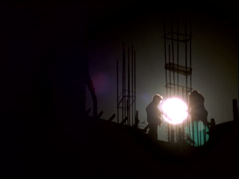 a golden hour sun silhouettes construction workers working with thin, steel rods on platform. - golden hour stock videos & royalty-free footage