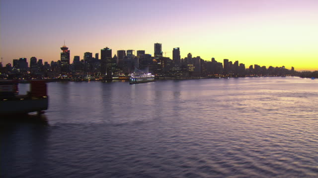 Golden Hour sunlight shines on the water of the Burrard Inlet and downtown Vancouver, Canada