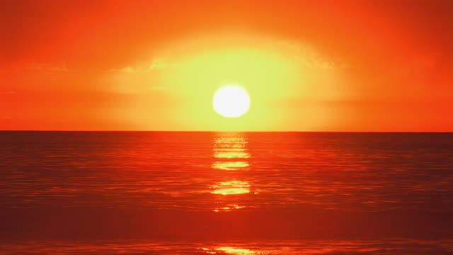 a golden idyllic california sunset as the sun sets into the waters of the gentle ocean surf - sunset stock videos & royalty-free footage