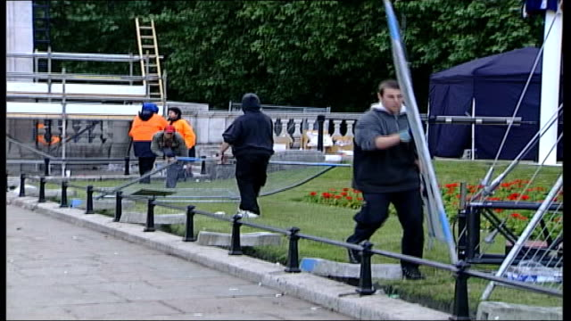 vídeos de stock e filmes b-roll de day after england london the mall empty orchestral stand on victoria memorial roundabout pan around to cleanup trucks vehicles men moving fences pan... - moving activity