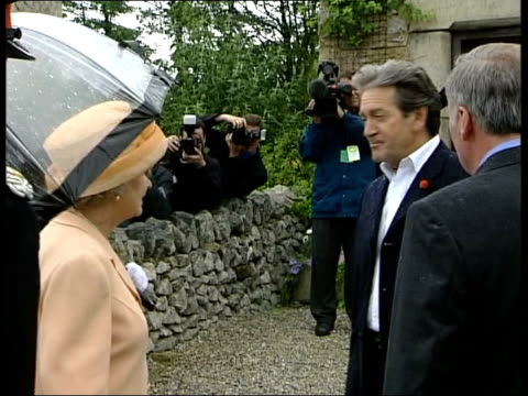 queen visits emmerdale itn england yorkshire harewood queen elizabeth ii puts up umbrella then along to tour emmerdale set pan ms side queen chatting... - cast member stock videos and b-roll footage