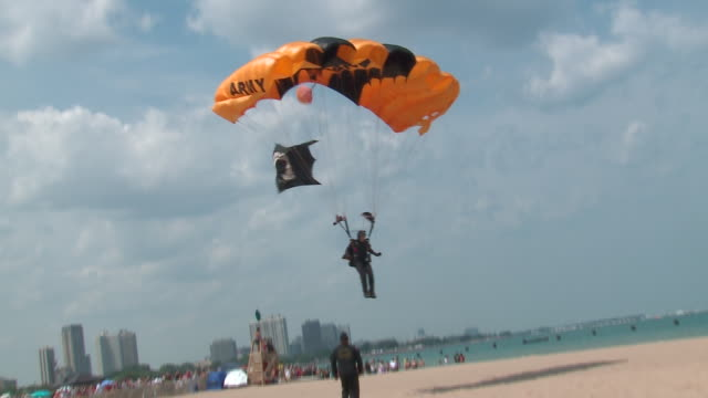 golden knights u.s. army parachute team member lands on beach during chicago air and water show on aug. 20, 2017. - chicago air and water show stock videos & royalty-free footage