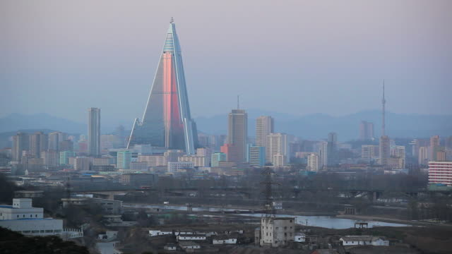 golden light shines on the ryugyong hotel in pyongyang. - pyongyang stock videos and b-roll footage