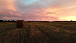 Golden multicolor sunset over a farm field with hay bales