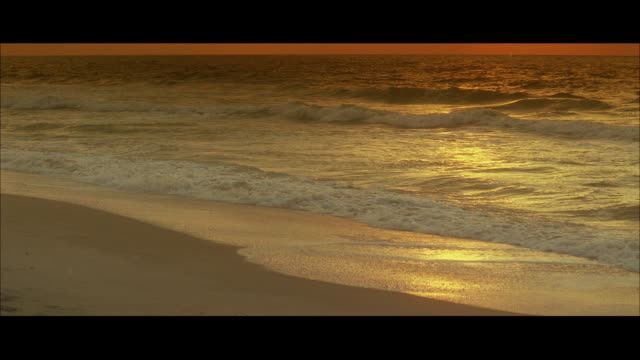 ms golden ocean waves on beach at sunset - letterbox format stock videos & royalty-free footage