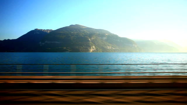 golden pass train travelling beside lake thun - train vehicle stock videos and b-roll footage