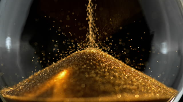slo mo ld golden sand falling down - hourglass stock videos & royalty-free footage