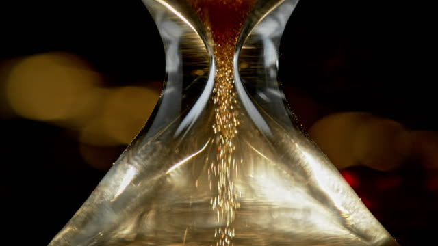 slo mo ld golden sand falling through an hourglass - hourglass stock videos & royalty-free footage