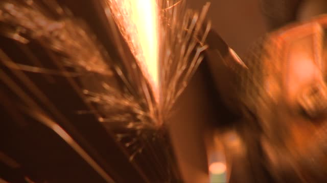 golden sparks fly from a grinder as it smooths a sheet of steel. available in hd. - grinding stock videos and b-roll footage