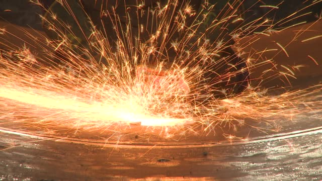 vidéos et rushes de golden sparks spray in a circle as a worker uses a grinder on a sheet of steel. available in hd. - tôle